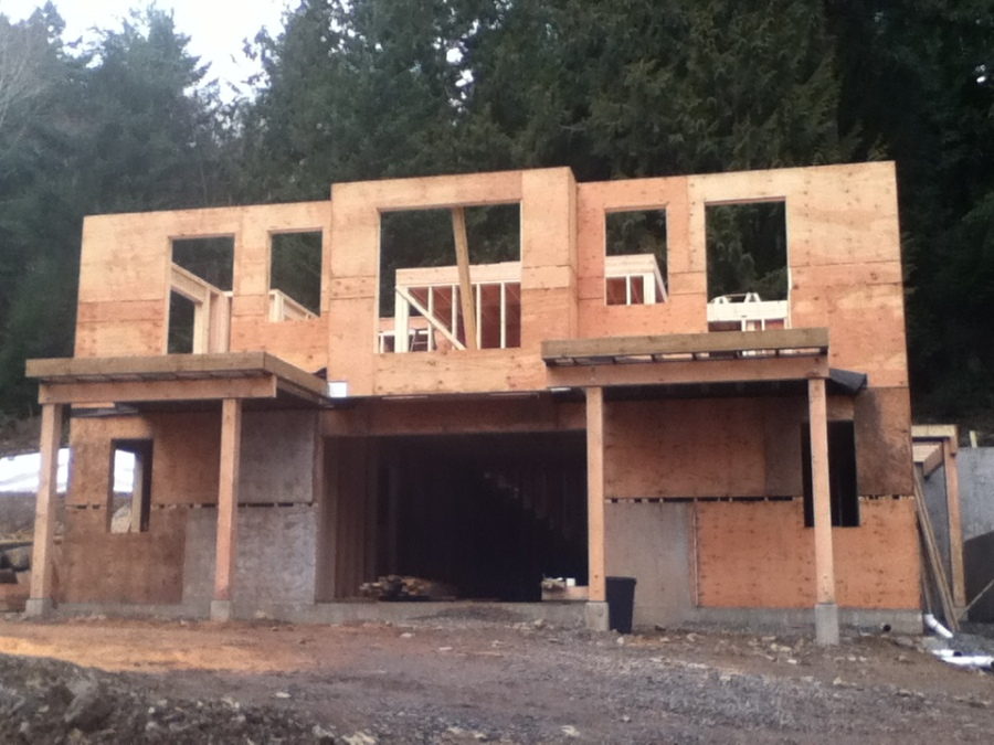 February 1: Lower level and Main Floor Framed. Here you can see the entrance to the Art Space, the two porches and overhangs sticking out in the front and, through the framed windows we can see the framed kitchen, on which will be a prayer loft.