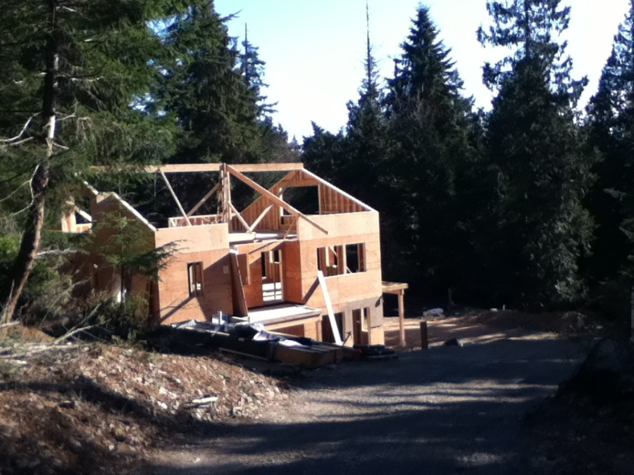 Here we see a view of the Main House from the top of the driveway. The roof is being framed and it is easy to see that there are going to be many windows to let in much light.